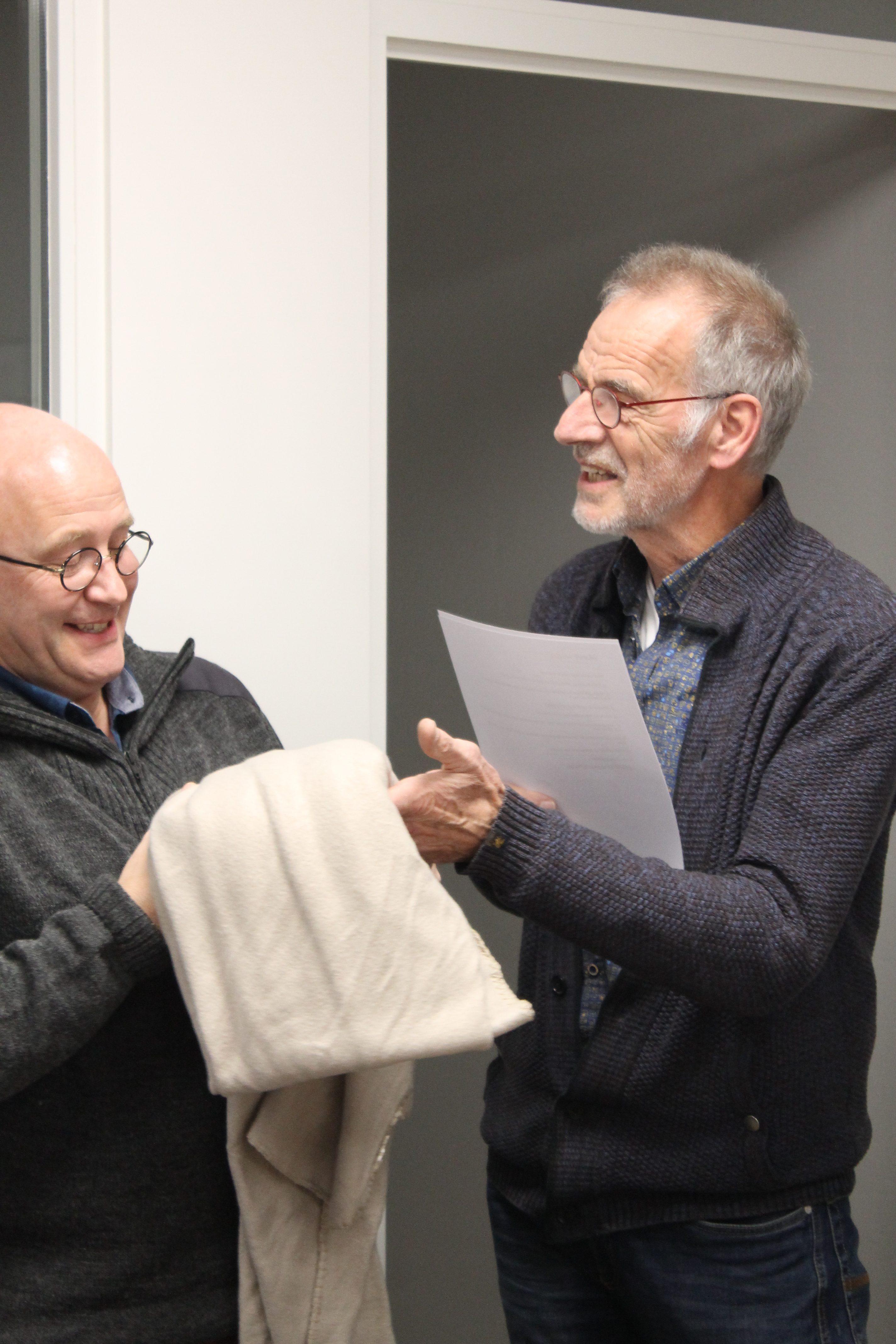 Klaas Kopinga overhandigt de nieuwe voorzitter John Brunekreeft een deken, als symbool voor de warmte die Meet-Inn haar gasten kan bieden